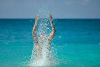 Happy Man Splashing Water In The Ocean